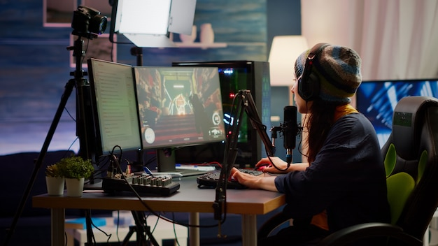 Frauenstreamer, der den ton mit einem professionellen mixer zum streamen von videospielen im gaming-heimstudio überprüft. profi-gamer, der ego-shooter-videospiele spielt und mit teamkollegen im offenen chat spricht