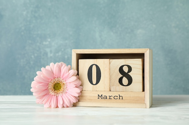 Frauentag 8. märz mit holzblockkalender. schönen muttertag. frühlingsblume auf weißem tisch