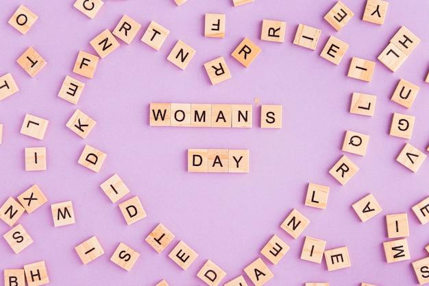 Frauentag geschrieben in scrabble-buchstaben, die eine herzform bilden