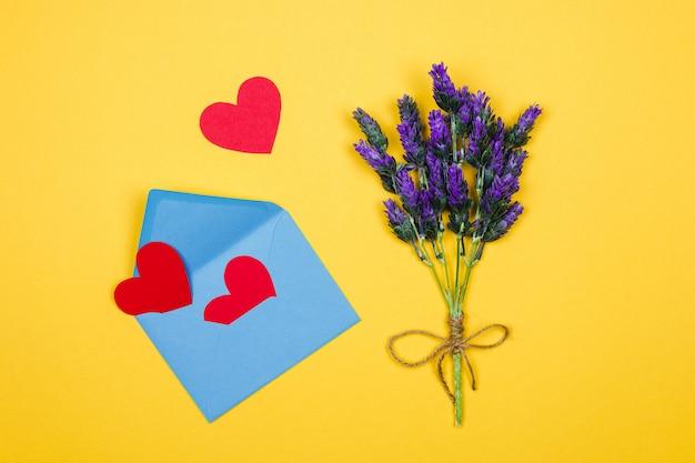 Frauentageskarte. lavendelzweig und blauer umschlag mit roten herzen auf gelbem hintergrund