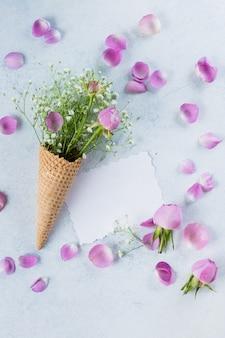 Frauentageskonzept der mutter. waffelkegel mit gypsophila mit rosa rosen und leerer grußkarte