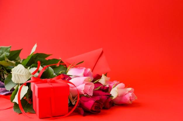 Frauentagskonzept und valentinstaggrußkarte. komposition mit geschenk, rosen und umschlag. platz für text.