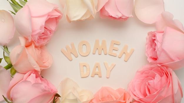 Frauentagsnachricht mit rosa rosenblume verziert auf weißem hintergrund
