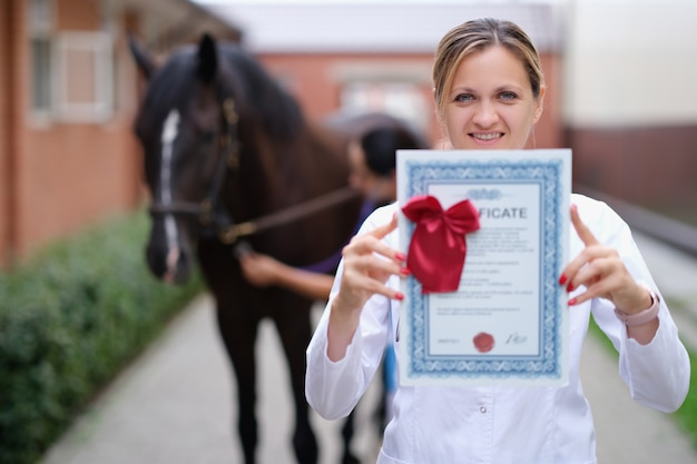 Frauentierärztin mit ausbildungszertifikat auf pferdehintergrund