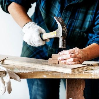 Frauentischler, der den hammer drückt nagel auf einem holz verwendet