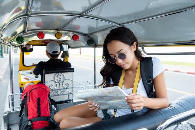 Frauentourist, der auf lokales tuk tuk-taxi in bangkok thailand reist