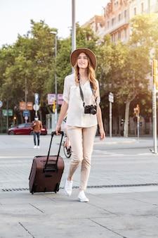 Frauentourist, der durch die stadt geht, die einen koffer und eine vintage-kamera trägt.