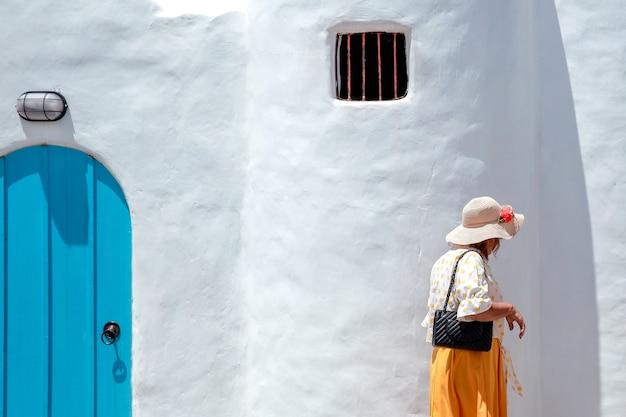 Frauentourist, der vor dem traditionellen griechischen haus von santorini geht?