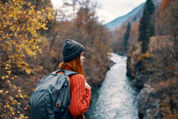 Frauentourist mit rucksack auf der brücke am fluss reisen