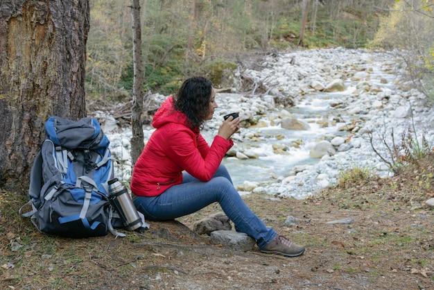 Frauentourist trinkt kaffee auf einem halt im wald durch den fluss.