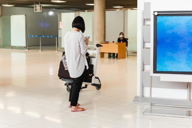 Frauentouristin am flughafen mit handy mit trolley-tasche.