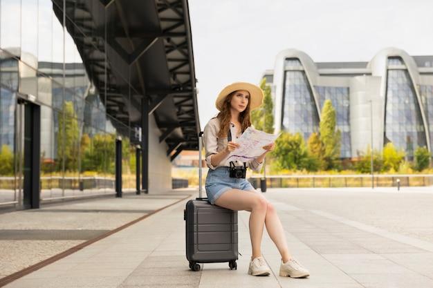 Frauentouristin, die auf ihrem koffer am bahnhof sitzt