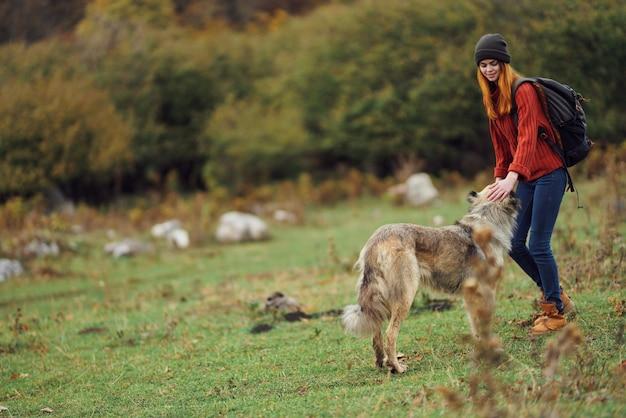 Frauentouristin mit hund, der in der naturreise geht, passieren die freiheit des abenteuers. hochwertiges foto