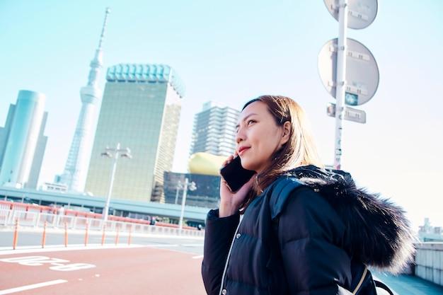 Frauentouristin mit smartphone in tokio japan