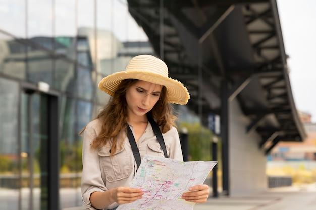 Frauentouristin untersucht eine karte der stadt