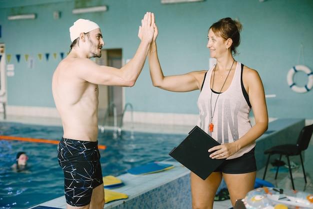 Frauentrainer, der dem schwimmer hohe fünf gibt. sie hält zwischenablage. erfolgskonzept.