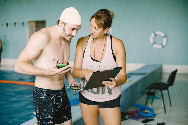 Frauentrainer, der schwimmer seine ergebnisse zeigt. sie hält klemmbrett und spricht mit mann.
