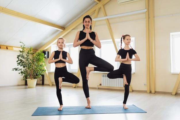 Frauentrainerin mit zwei schülern in schwarzer sportbekleidung, die yoga praktizieren, führen eine vrikshasana-übung auf einer turnmatte oder einer baumpose mit namaste durch, die in einem yoga-studio trainiert