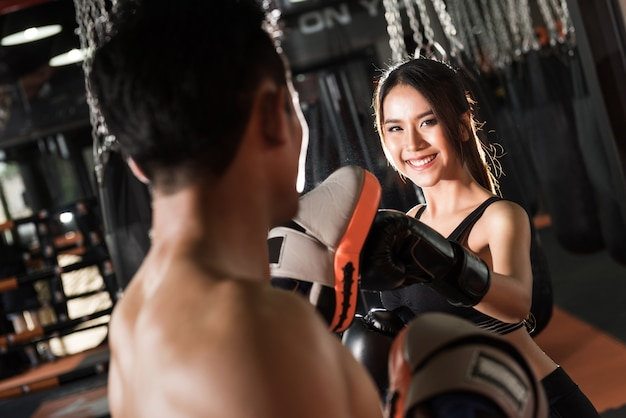 Frauentraining mit boxhandschuhen an der turnhalle, paare, die das stempeln ausüben