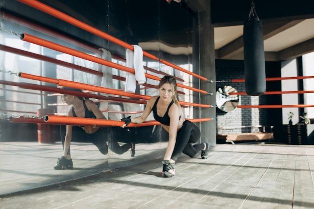 Frauentrainings-morgentraining in der turnhalle. junge frau, die turnhallentraining in der turnhalle tut