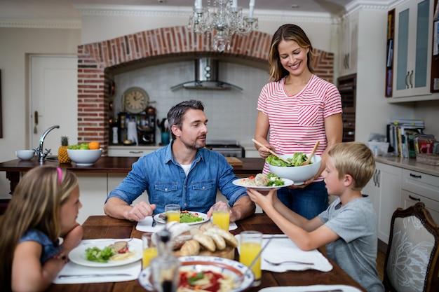 Frauenumhüllungslebensmittel zu ihrer familie in der küche