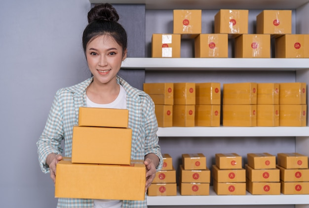 Frauenunternehmer mit paketkästen in ihrem eigenen job, der zu hause onlinegeschäft kauft