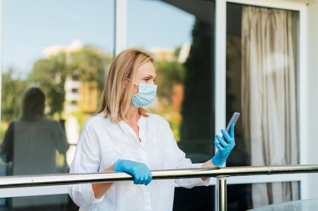 Frauenvideoanruf mit medizinischer maske und handschuhen