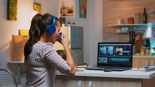 Frauenvideoeditor mit kopfhörer, der mit filmmaterial und ton arbeitet, der in der heimküche sitzt. frau videofilmer, die audiofilmmontage auf professionellem laptop bearbeitet, der um mitternacht auf schreibtisch sitzt