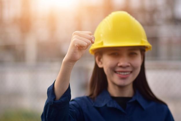 Frauenvorarbeiter-schutzhelm, der handerfolg hält