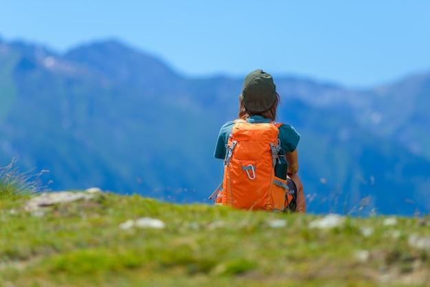 Frauenwanderer auf berggipfel mit rucksack und trekkingstöcken, selektiver fokus rückansicht, alpen im hintergrund, sommer-fitness-wohlbefinden