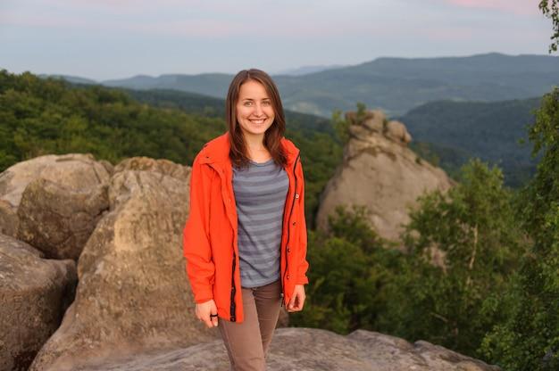 Frauenwanderer auf großem felsen auf den berg
