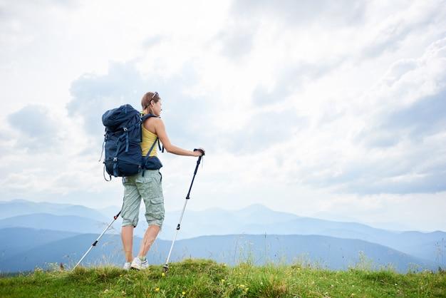 Frauenwanderer, der auf grasartigem hügel, tragender rucksack, unter verwendung der wanderstöcke in den bergen wandert