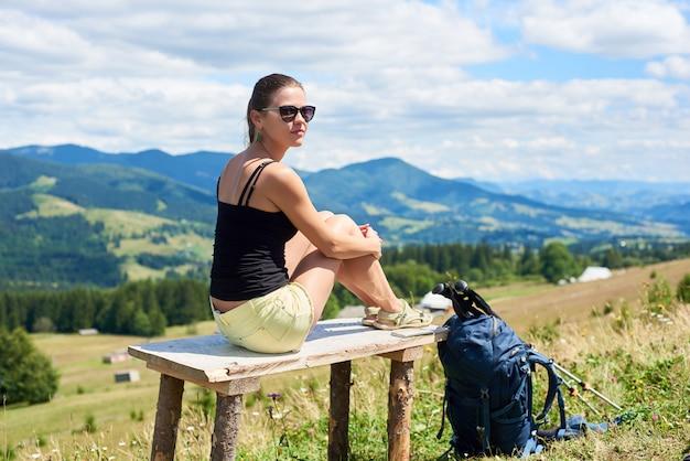 Frauenwanderer, der auf grasbewachsenem hügel wandert, rucksack tragend, mit trekkingstöcken in den bergen