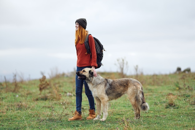 Frauenwanderer, der den hund in den bergen reist
