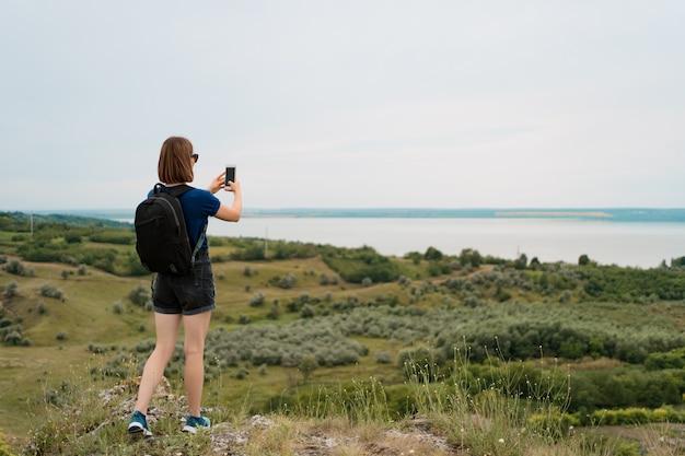 Frauenwanderer, der foto mit smartphone am hügelgipfel nimmt.