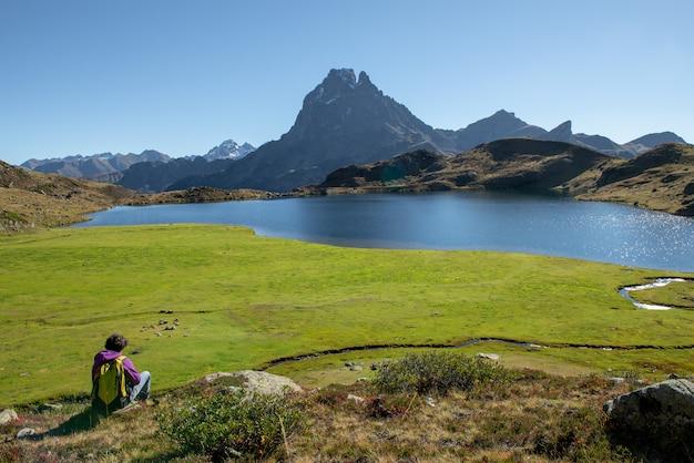 Frauenwanderer, der in den pyrenäen-bergen nahe dem pic du midi d ossau sitzt
