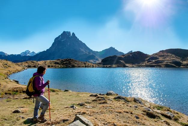 Frauenwanderer, der in die pyrenäen-berge nahe dem pic du midi d ossau geht