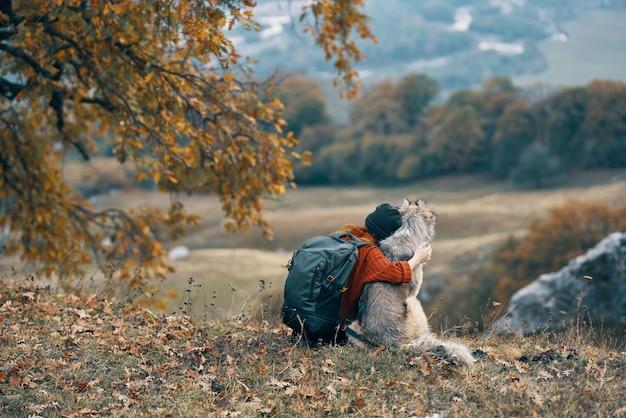 Frauenwanderer, der mit hund auf natur in den bergen reisefreundschaft umarmt