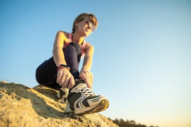 Frauenwanderer, der schnürsenkel ihrer sportstiefel bindet, während an einem sonnigen tag steiler großer felsen klettert.