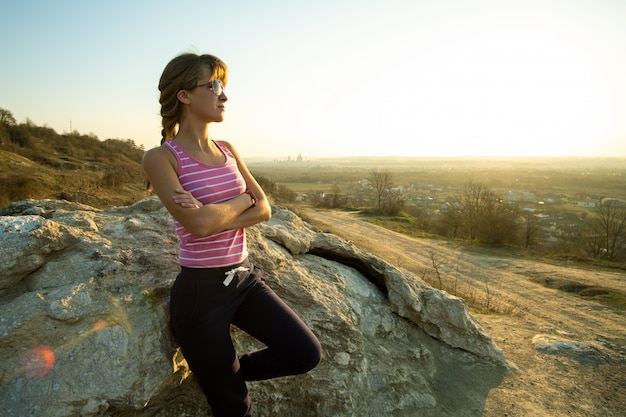 Frauenwanderer, der sich auf einen großen felsen stützt, der warmen sommertag genießt. junger weiblicher kletterer, der während der sportaktivität in der natur ruht. aktive erholung im naturkonzept.