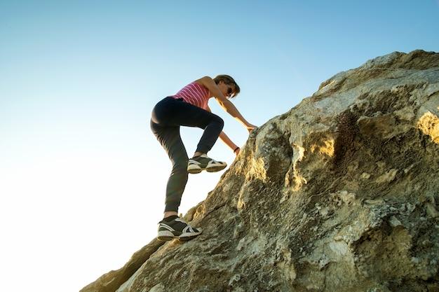 Frauenwanderer, der steilen großen felsen an einem sonnigen tag klettert
