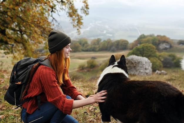 Frauenwanderer in der natur neben hundelandschaft reisen zum herbstwald