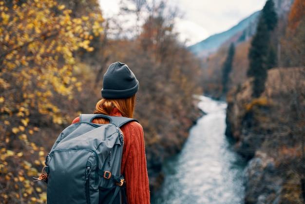 Frauenwanderer mit einem rucksack auf ihrem rücken nahe einem gebirgsfluss in der naturrückansicht