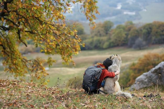 Frauenwanderer mit hund in der natur bewundern die gebirgsreise
