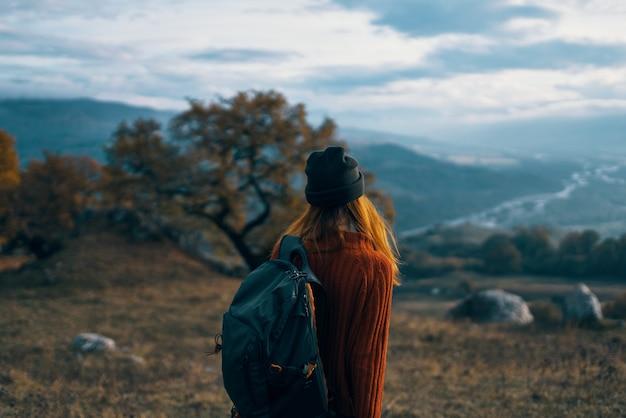 Frauenwanderer mit rucksack auf naturlandschaftshund