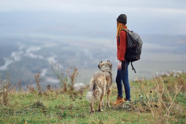 Frauenwanderer mit rucksack mit hund in den bergen reisen freundschaft
