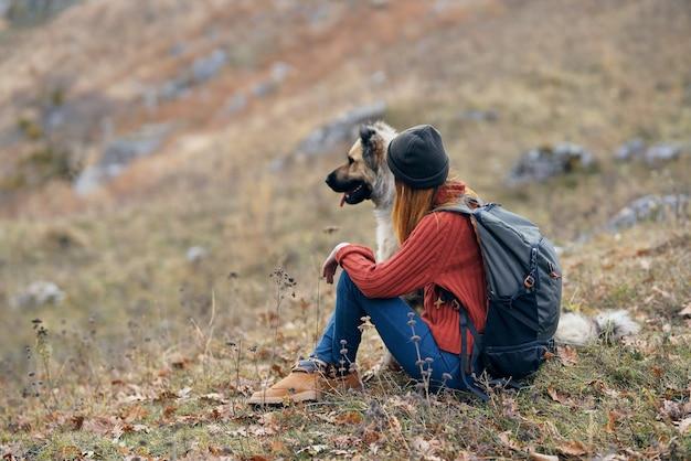 Frauenwanderer neben einem hund in den bergen auf naturferienlandschaft