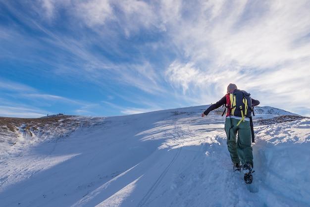 Frauenwanderertrekking auf schnee auf den alpen.