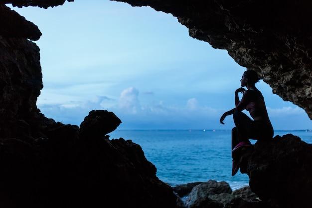 Frauenwartezeitsonnenuntergang in balinesse höhle am ozeanstrand.