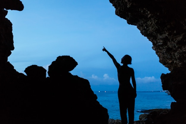 Frauenwartezeitsonnenuntergang in balinesse höhle am ozeanstrand,